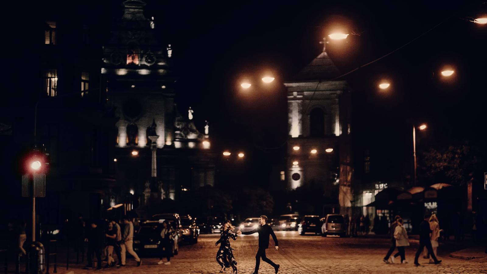 Dos joves creuant un carrer de nit, a París
