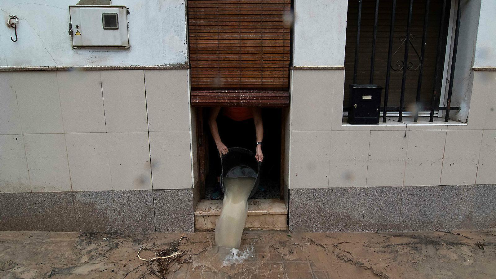 Un veí traient aigua de casa seva, inundada pel temporal, a Ontinyent.