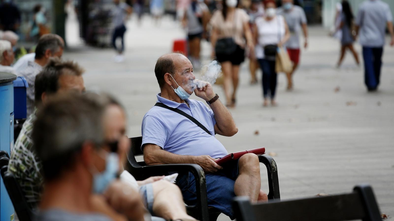 Un home fuma assegut en un banc al mig del carrer a Barcelona amb la mascareta desplaçada per sota el coll. Imatge del 18 d'agost del 2020, el dia que entra en vigor la prohibició de fumar al carrer si no es pot mantenir la distància de seguretat arran de la pandèmia del covid-19