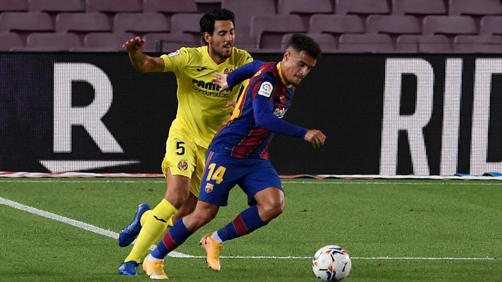 El jugador del Barça Coutinho controla una pilota davant del migcampista del Vila-real Parejo.