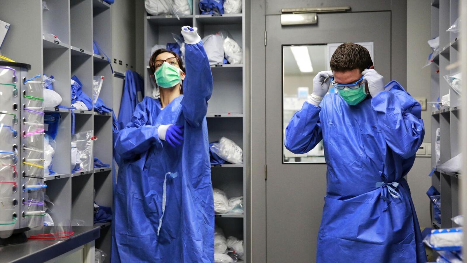 Sanitaris es posen el vestuari de protecció.