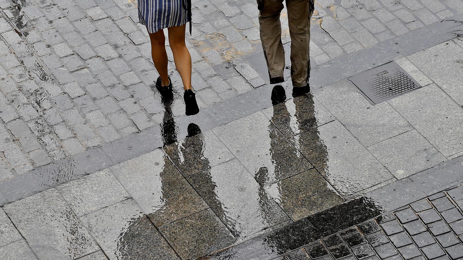 Dues persones caminen pel carrer mentre plou.