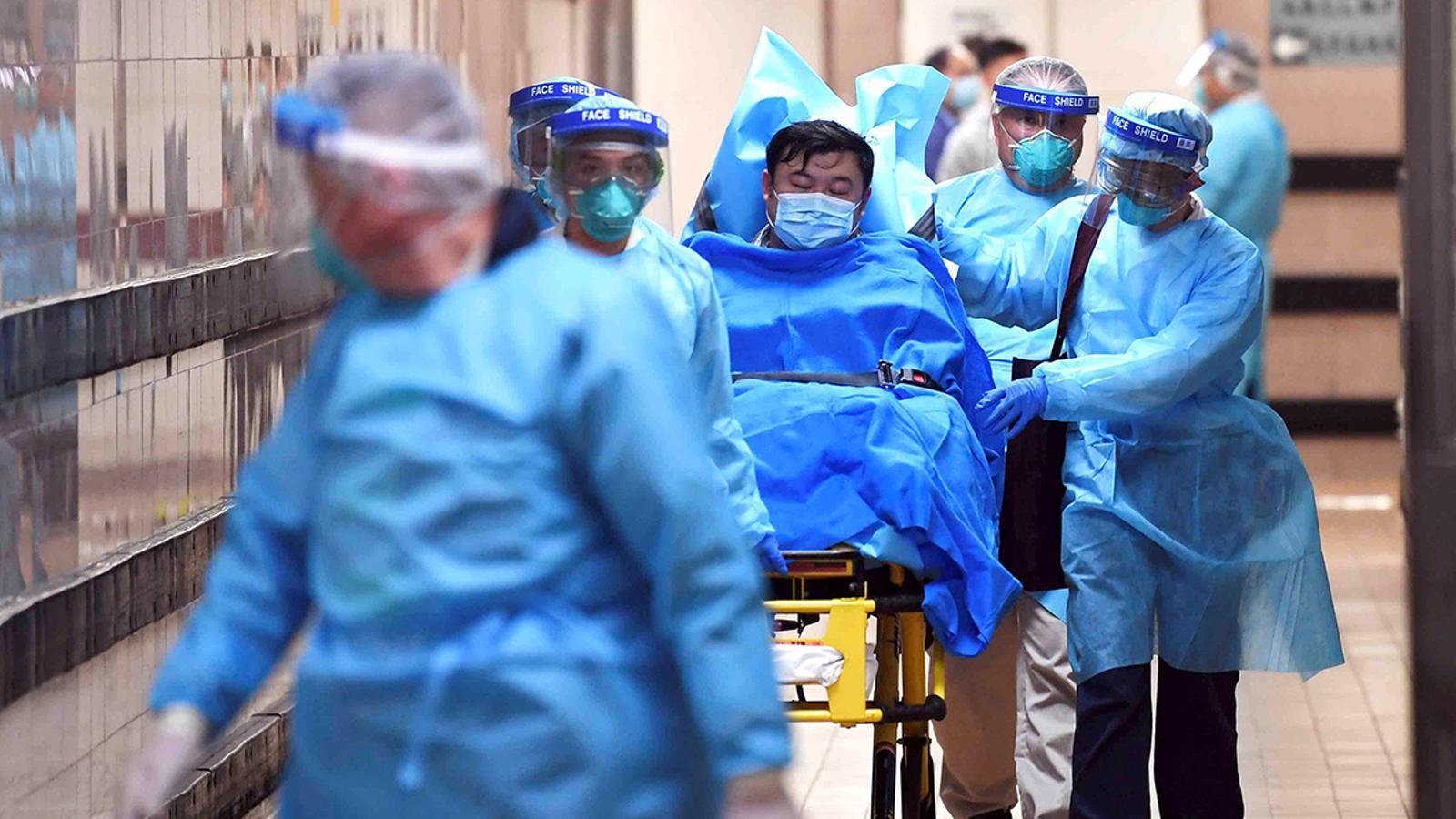 El personal mèdic trasllada a un pacient sospitós de patir coronavirus a l'Hospital Queen Elizabeth de Hong Kong