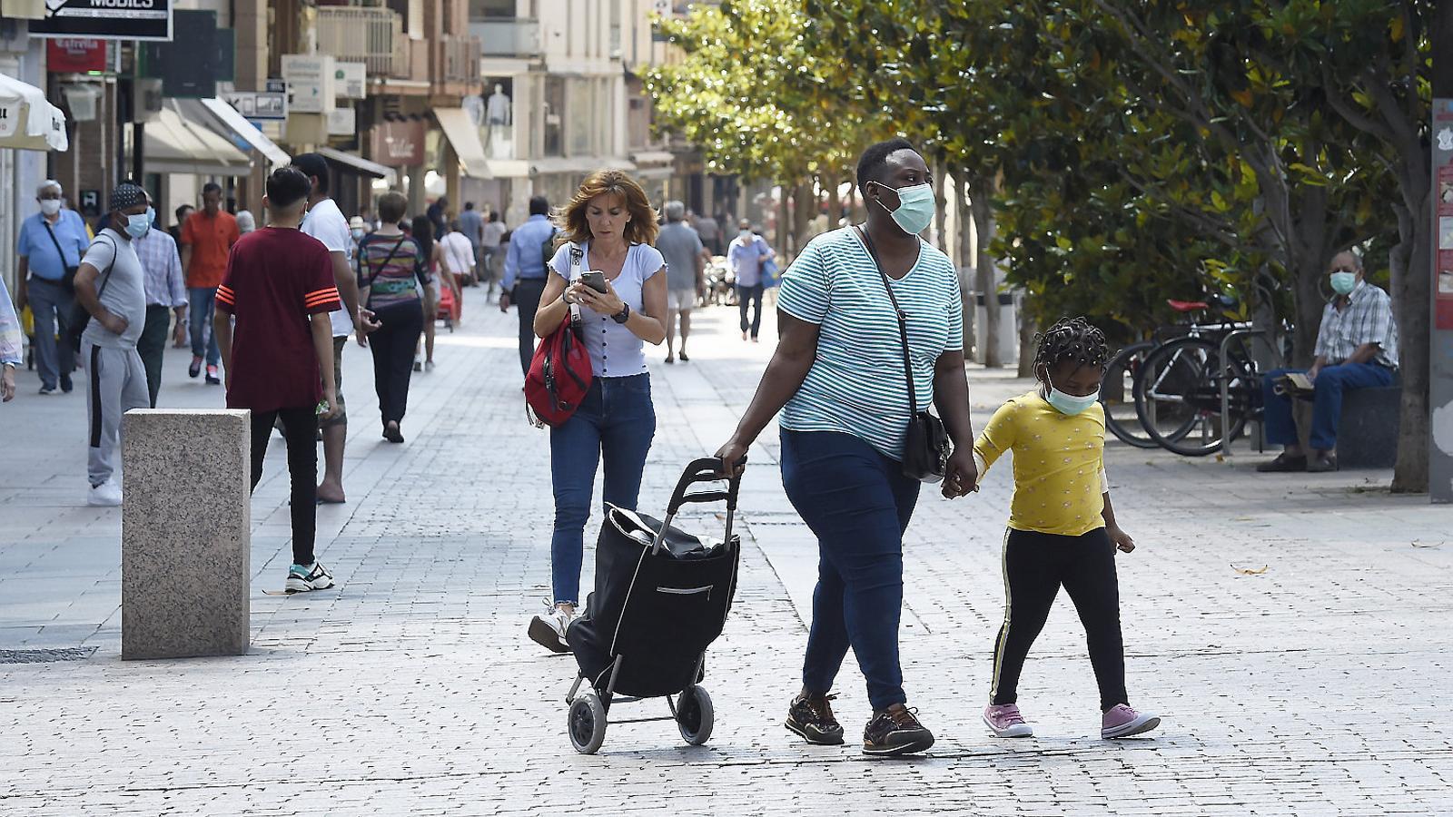 Ciutadans de Lleida passejant per la plaça de l'Auditori ahir.