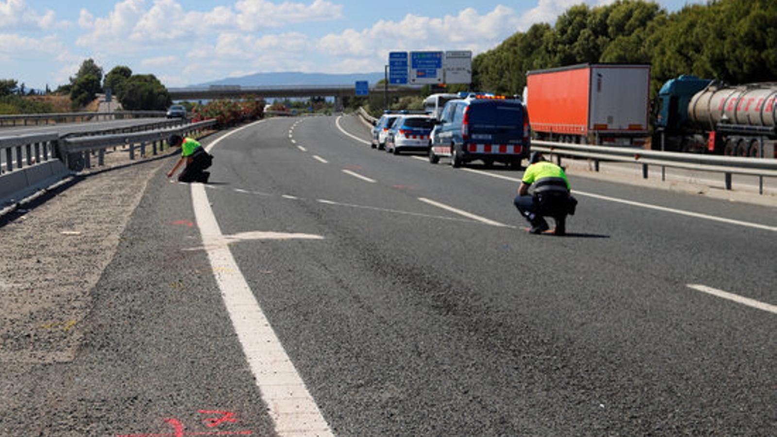 Dos agents dels Mossos d'Esquadra treballant en la investigació de l'accident on ha mort un motorista