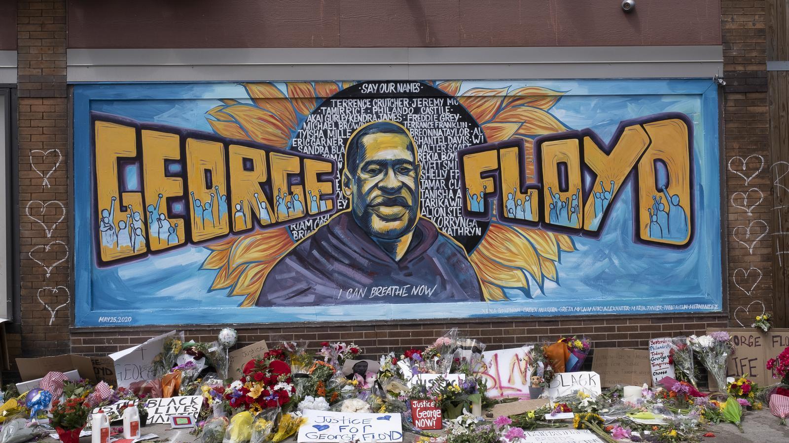Un mural en memòria de George Floyds ple de flors i de missatges reclamant la pau, a Minneapolis