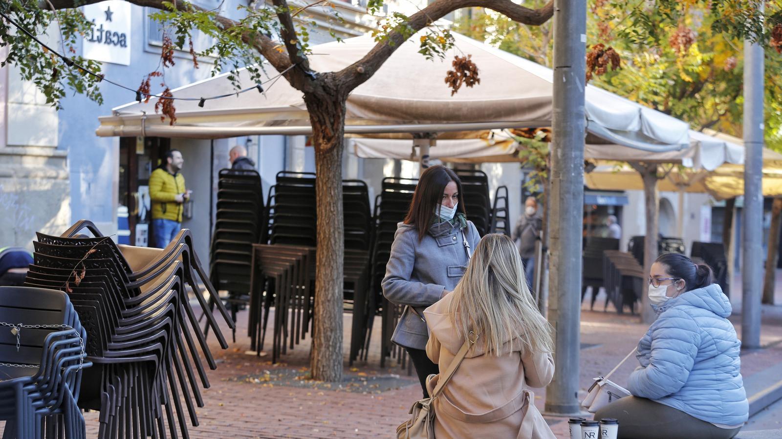 Tres clientes fan el cafè al carrer el primer dia de bars tancats a Terrassa