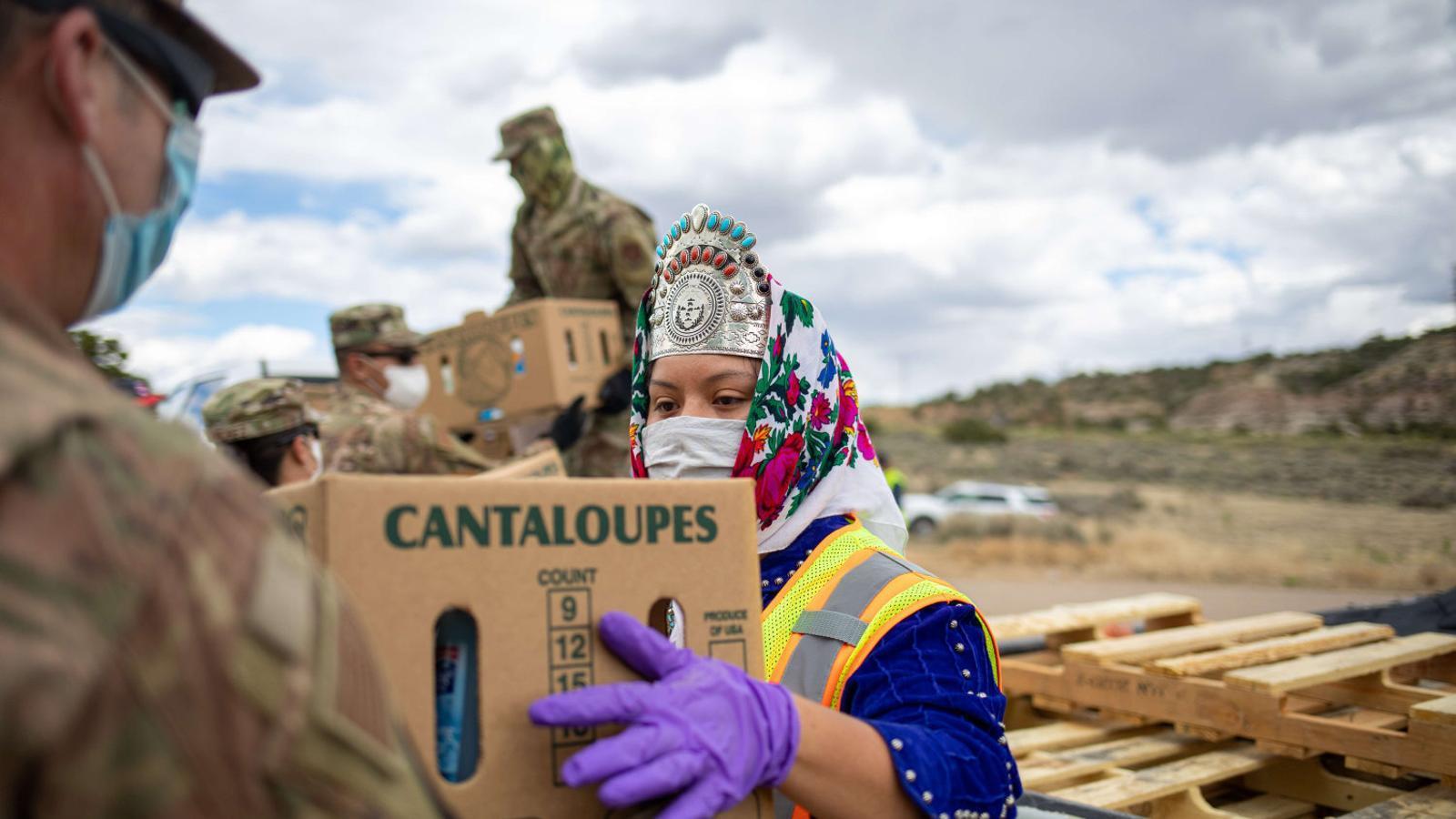 Una representant del poble navajo, amb mascareta i guants, repartint ajuda acompanyada de l'exèrcit a la Reserva Navajo, que s'estén per Nou Mèxic, Utah i Arizona.