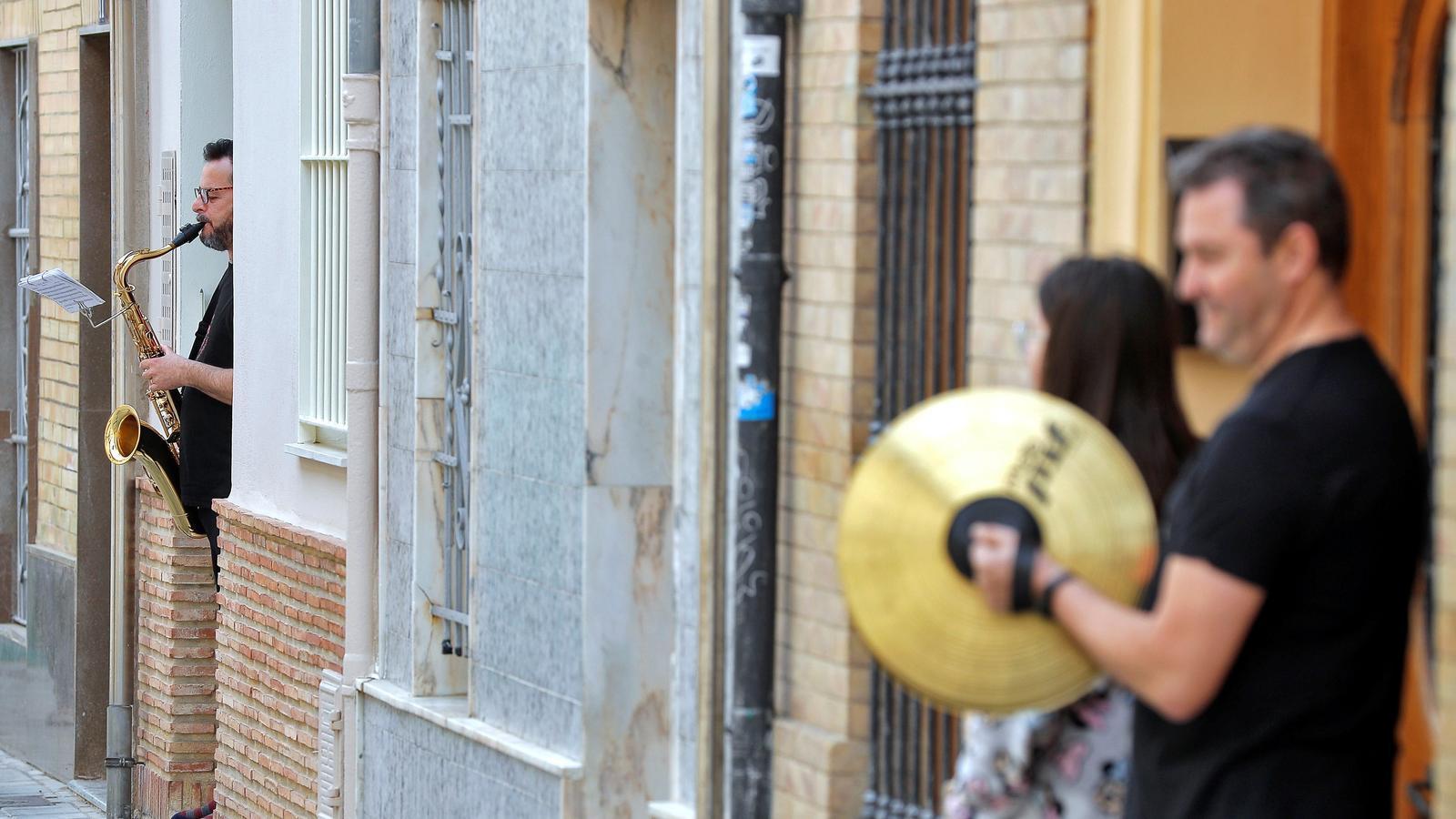 Diversos músics interpretant elspasdobles 'Paquito el Chocolatero' i 'Amparito Roca' a les portes de les seves vivendes