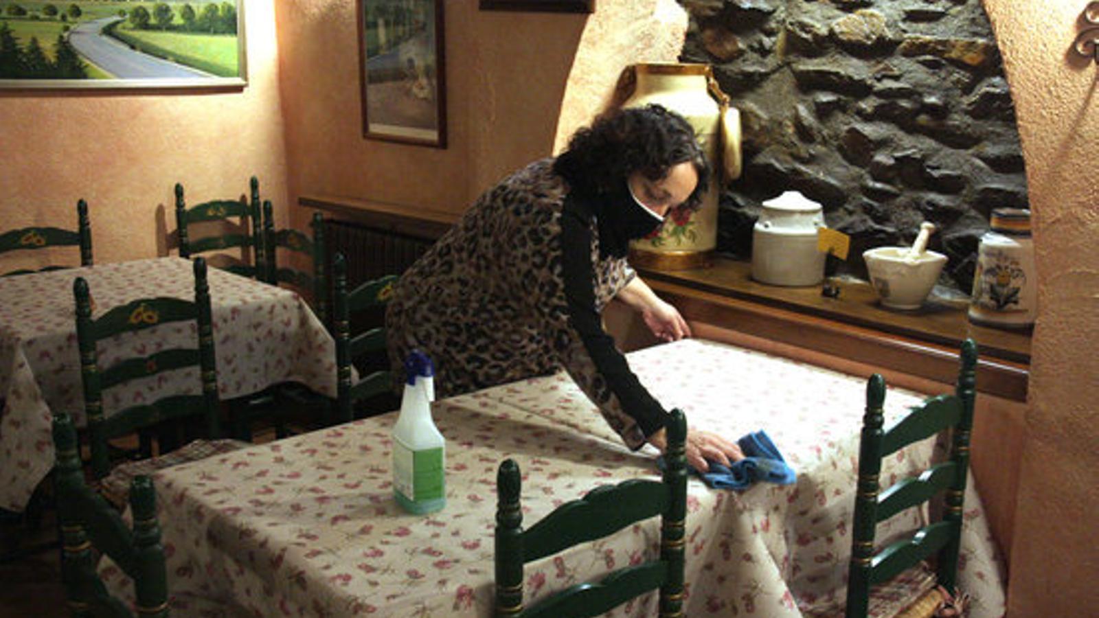La presidenta de l'Associació de Bars i Restaurants de la Cerdanya, Nativitat Bover, neteja una de les taules del seu establiment situat a Alp. / ACN
