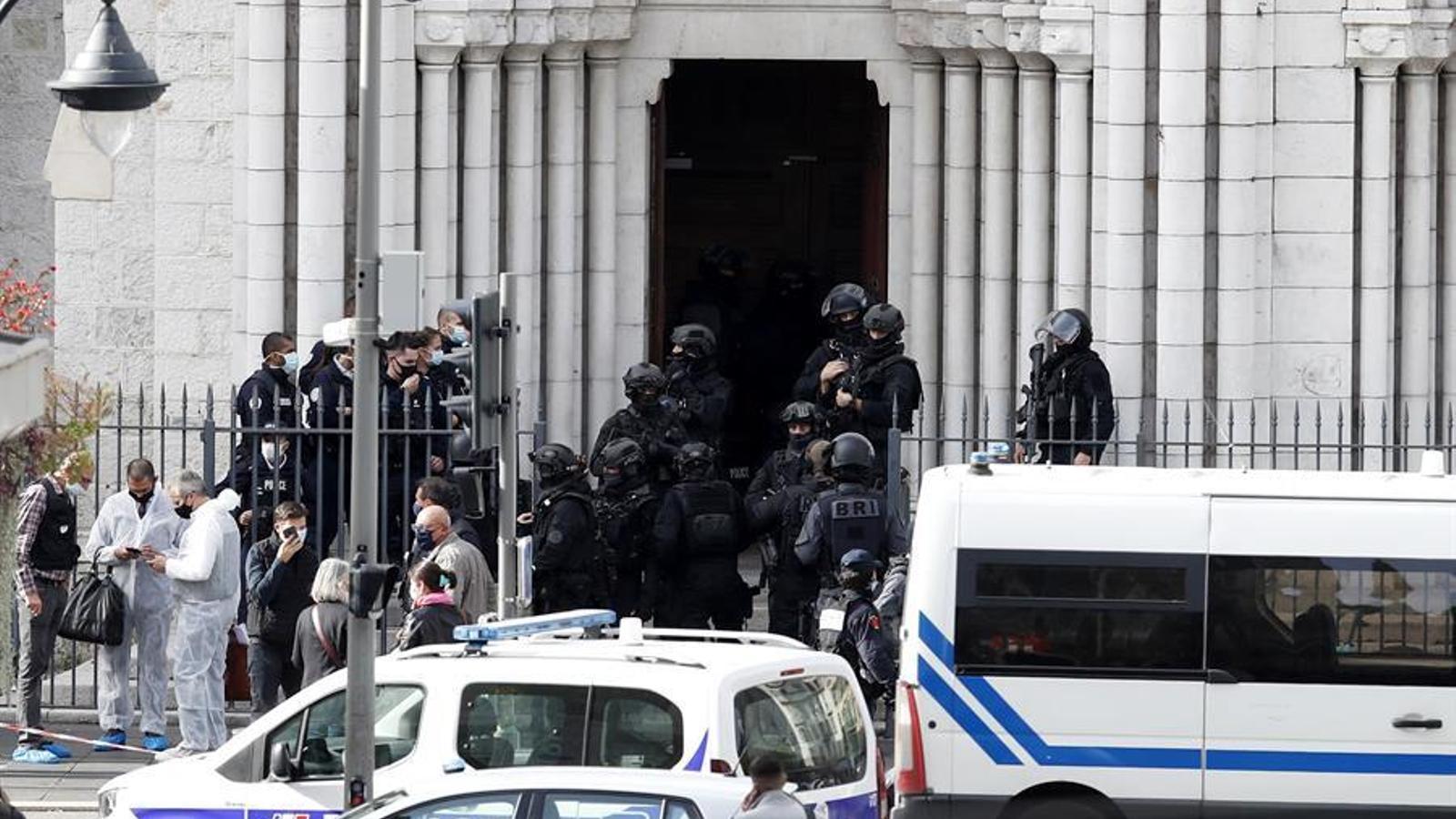 Agents de la policia nacional francesa a la porta de la basílica de Notre-Dame de l'Assumpció de Niça, després de l'atemptat d'aquest dijous al matí