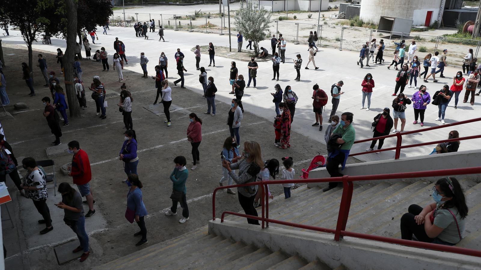 Desenes de xilens fan cua, amb distància de seguretat entre ells degut a la pandèmia, per votar aquest diumenge a Santiago.