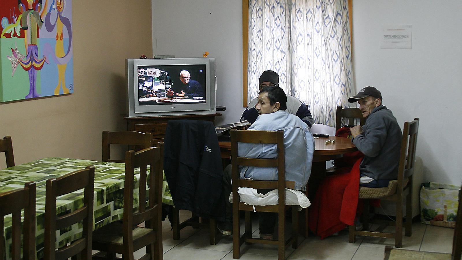 Diverses dependències del centre: el menjador, amb alguns usuaris; l'estança  dels homes i el petit pati interior on s'aireja el calçat.