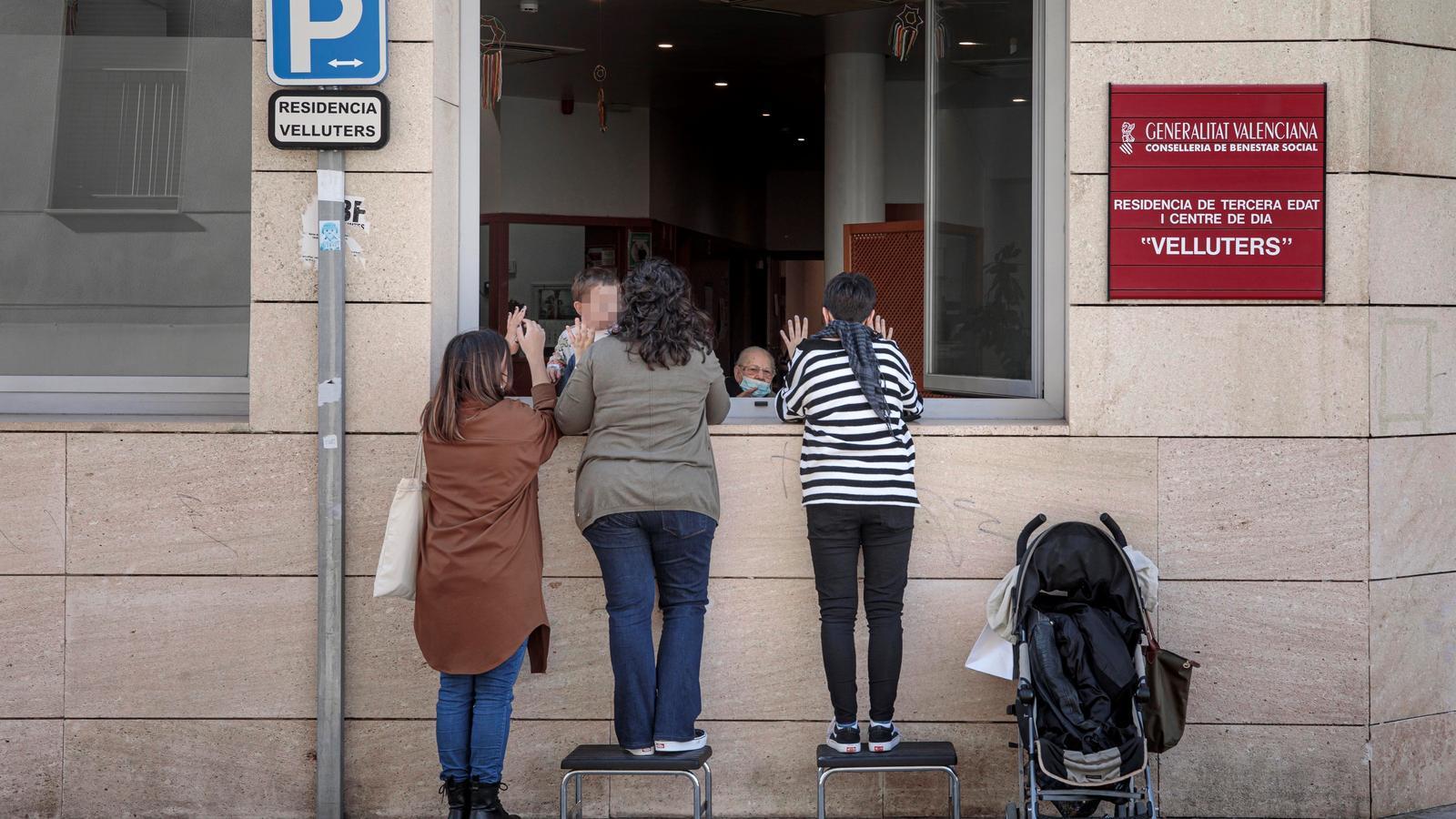 Una resident rep la visita de les seves netes a través d'una finestra del geriàtric del barri de Velluters de València