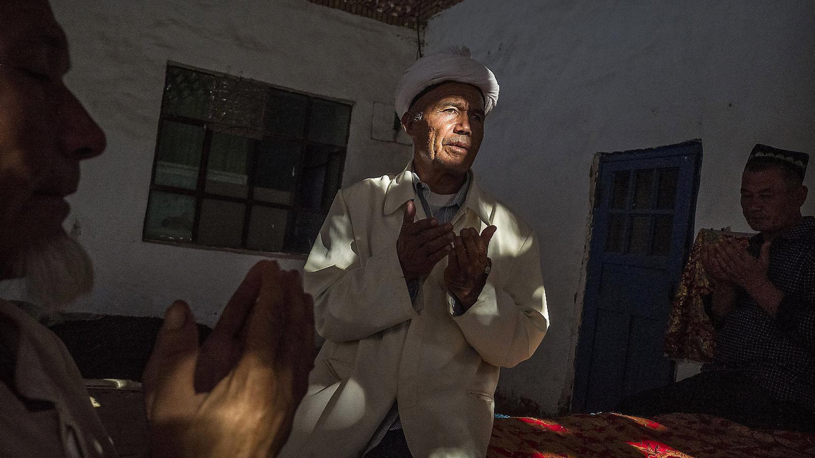 Un home uigur resant durant la festa del sacrifici del 2016 a la província xinesa de Xinjiang, on hi ha majoria de musulmans, molt perseguits pel govern xinès.