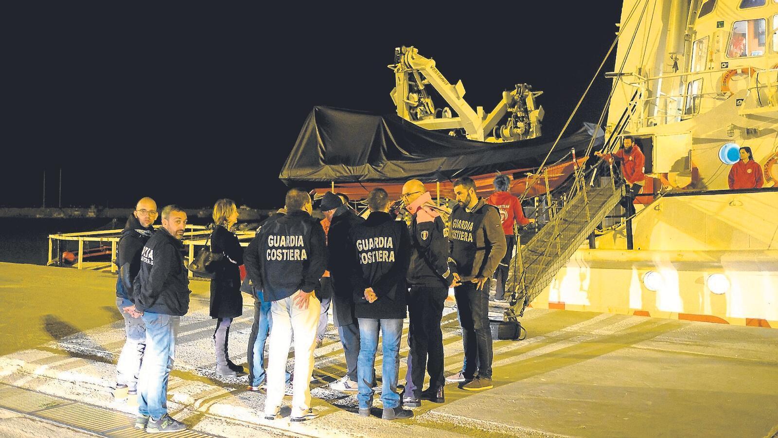 Guardacostes italians conversant amb els membres de la tripulació de l''Open Arms', al port sicilià de Pozzallo.