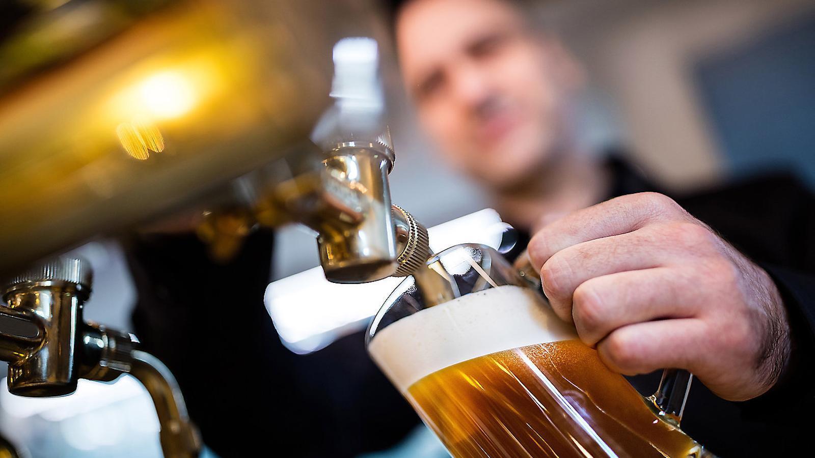 Un cambrer omplint una gerra de cervesa.