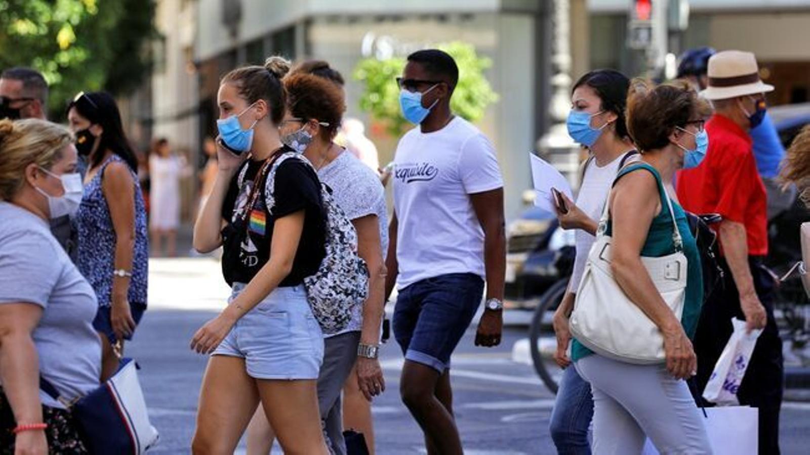 Diverses persones creuant un pas de vianants a la ciutat de València, en una imatge d'arxiu