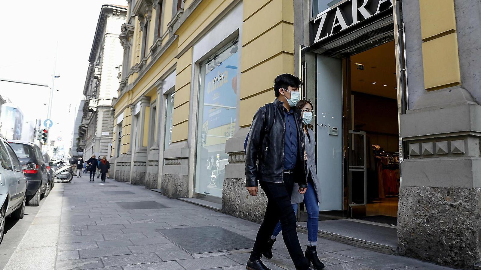 Una parella amb màscares passant per davant del Zara del Corso Buenos Aires, a Milà.