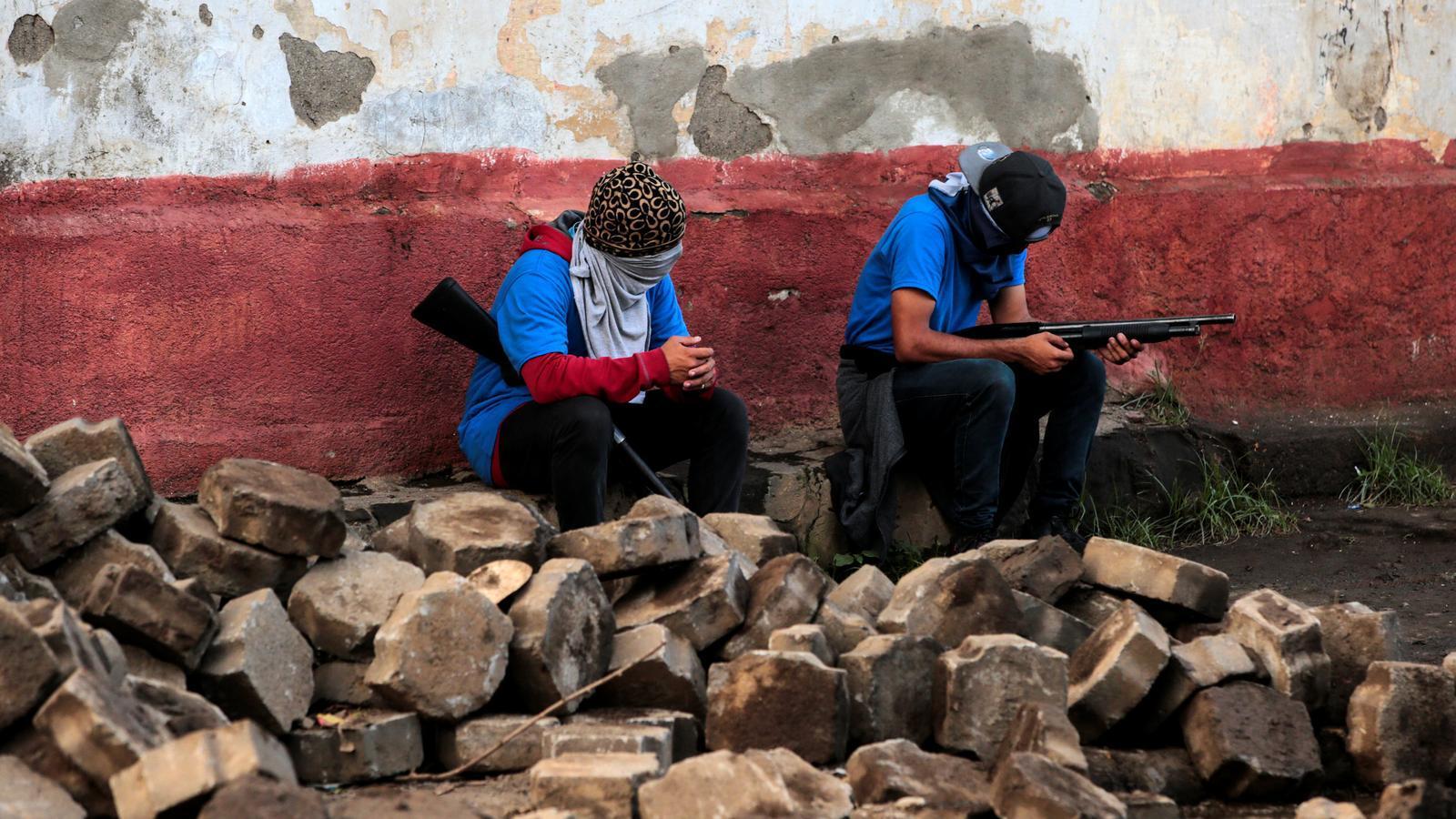 Dos encaputxats simpatitzants del president Ortega descansen després de l'ofensiva contra la població en vigílies de l'aniversari del triomf de la Revolució