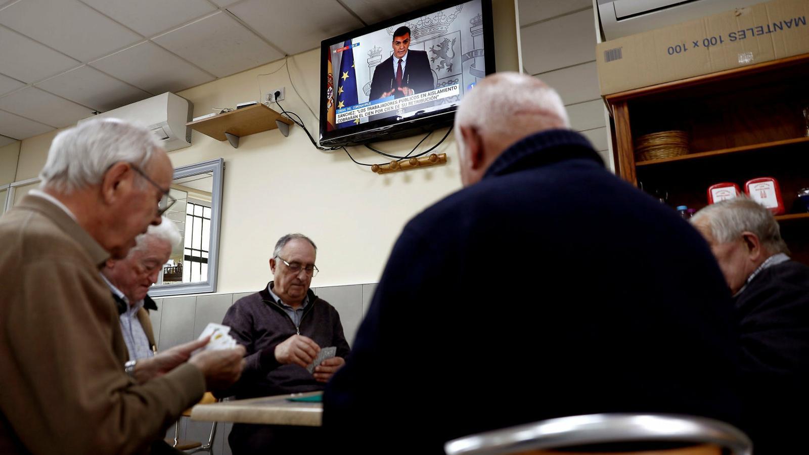Un grup d'homes jugant a cartes en un bar de Madrid durant la roda de premsa de Pedro Sánchez.