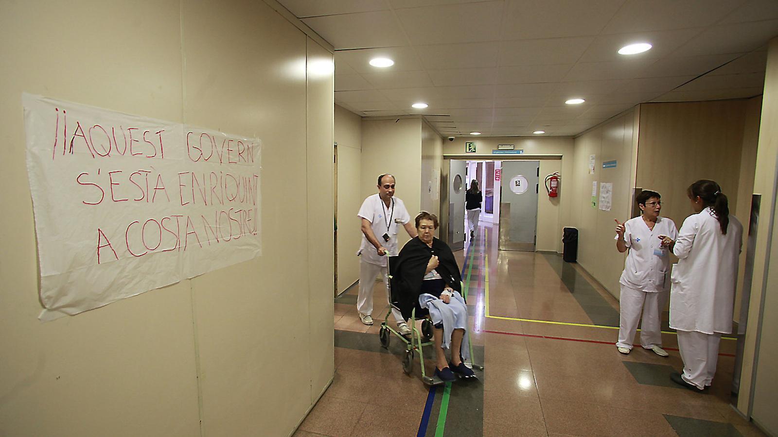 Personal mèdic i una pacient en un dels passadissos de l'Hospital de la Vall d'Hebron. / MANOLO GARCIA