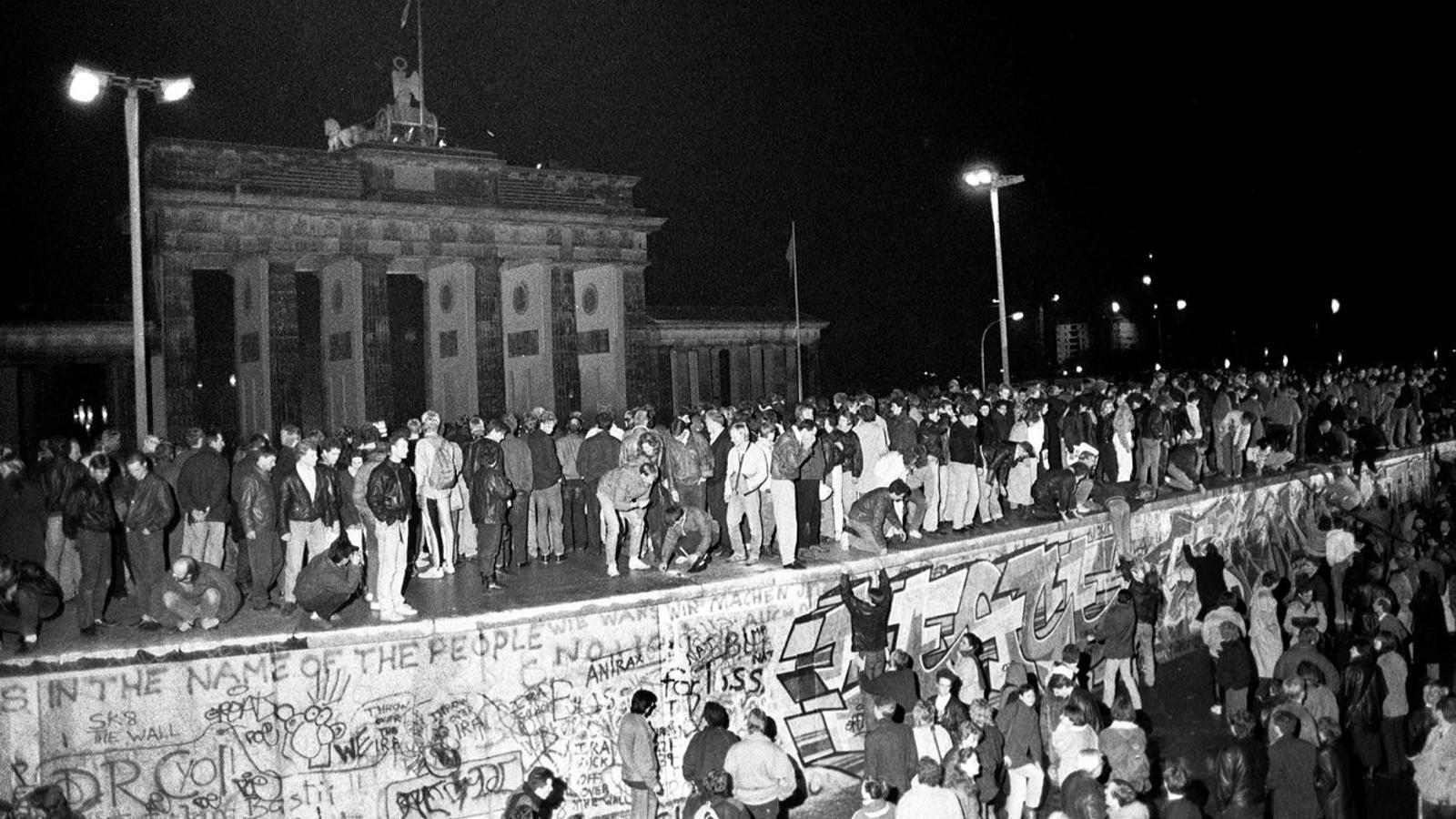 Ciutadans de Berlín Est i Oest celebrant dalt del Mur l'obertura de fronteres, la nit del 9 de novembre del 1989
