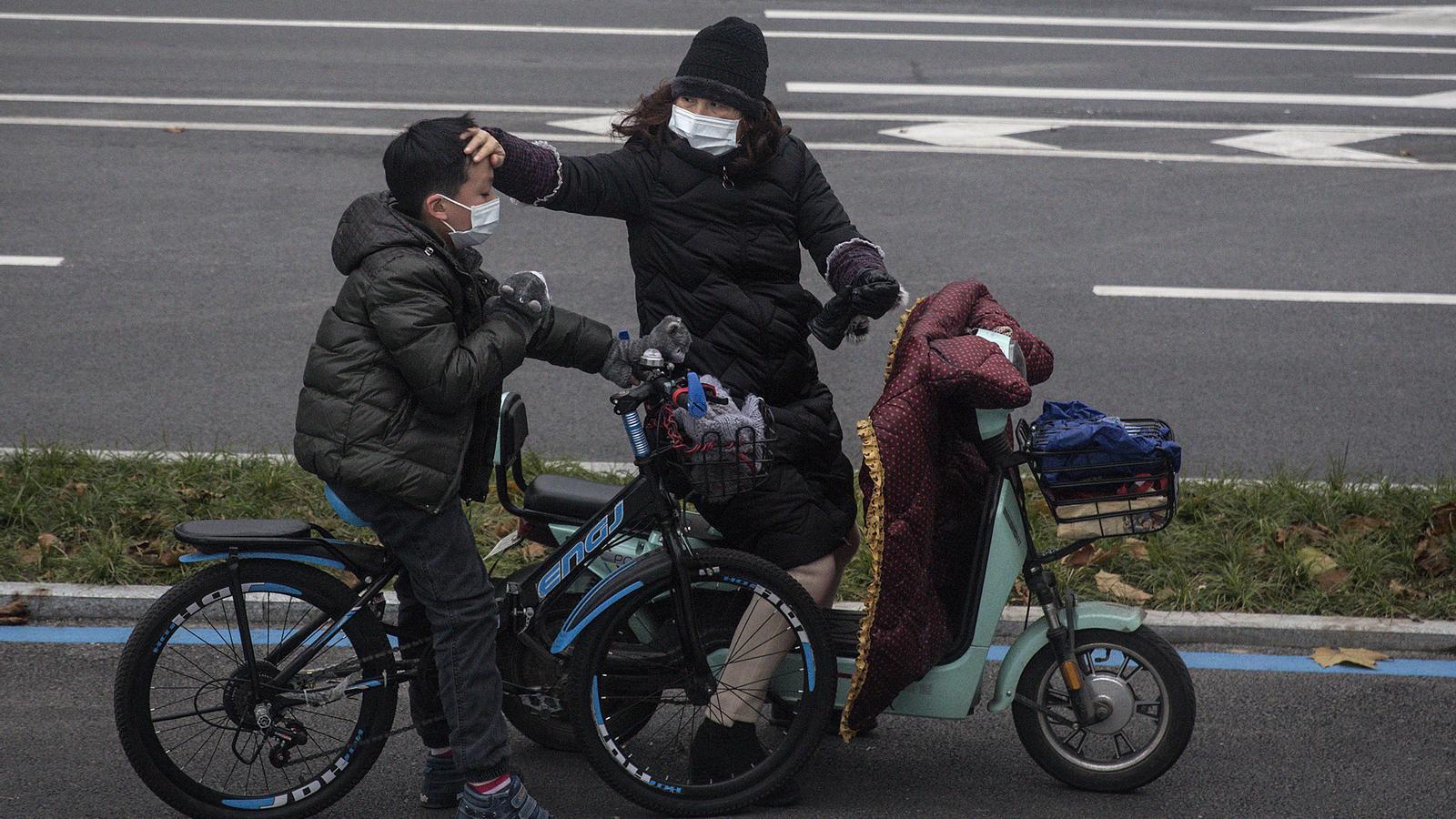 Una dona comprova si el seu fill té febra a Wuhan, Xina