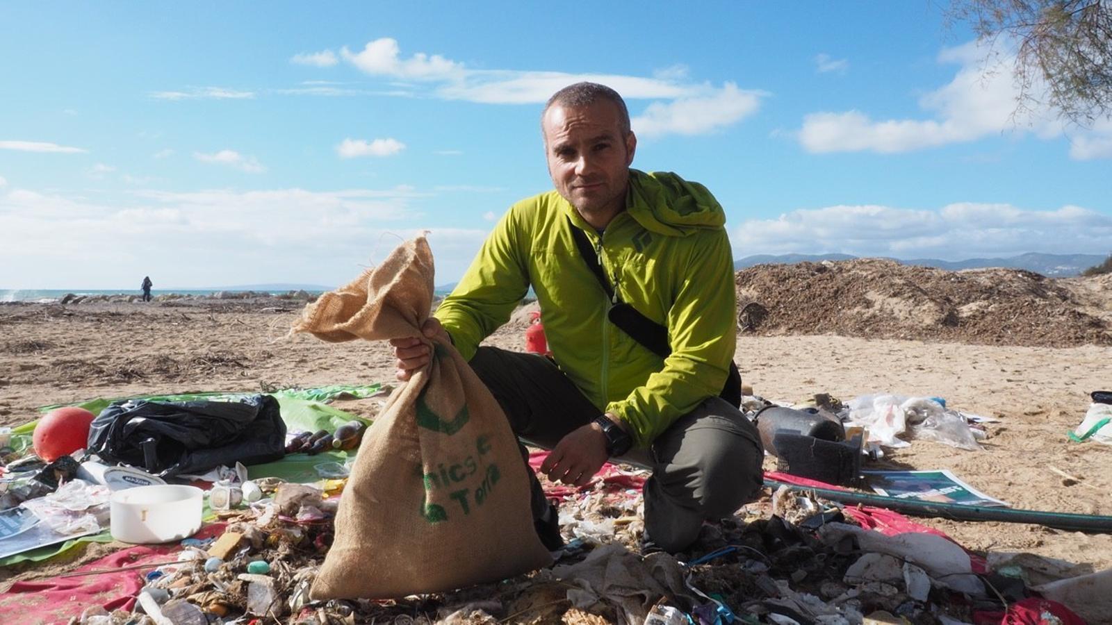 Daniel Gálvez recull productes plàstics abandonats a la platja.