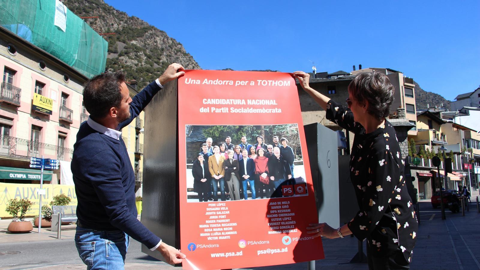 El cap de llista i la número dos, Pere López i Susanna Vela, a la penjada del primer cartell nacional a Andorra la Vella. / M. M.