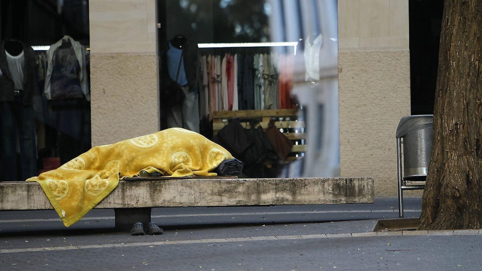 Una persona sense sostre dorm a un banc d'un carrer del centre de Palma