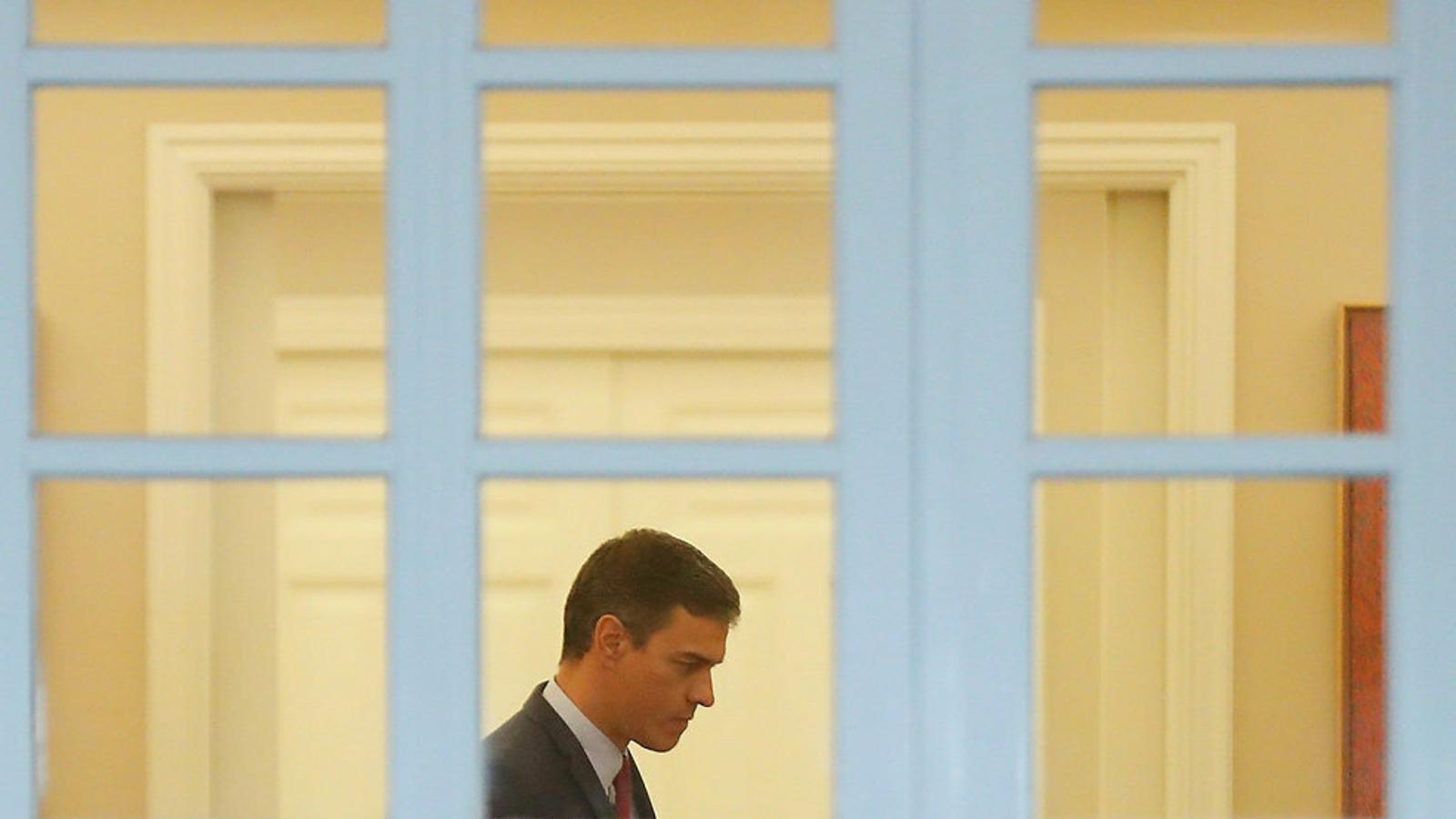 Pedro Sánchez passejant reflexiu pels passadissos de la Moncloa.