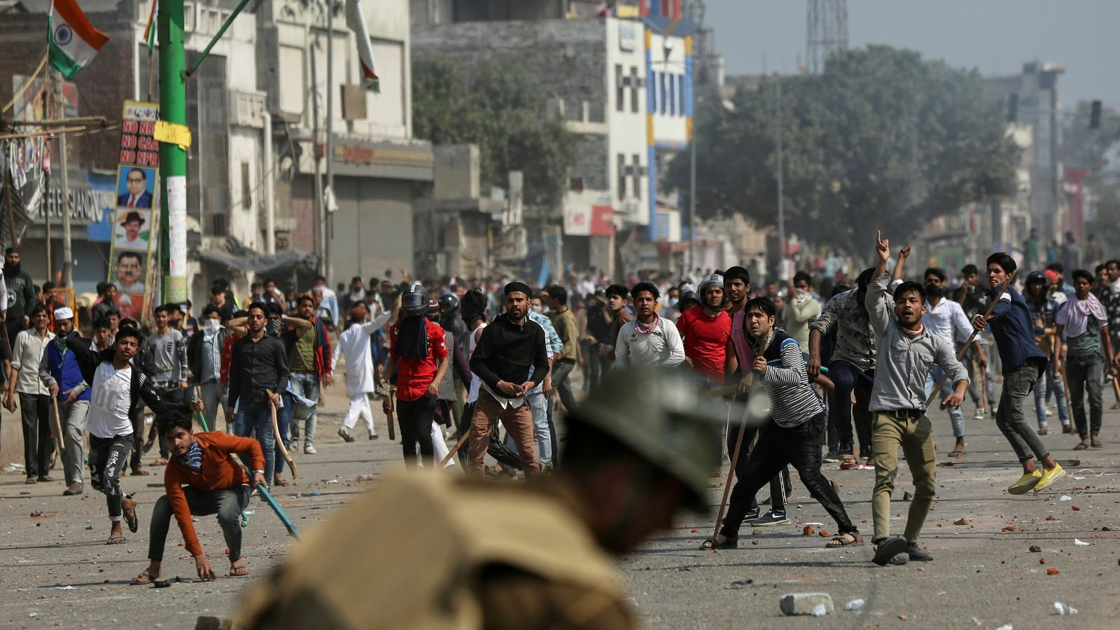 Manifestants opositors a la nova llei de ciutadania llencen pedres contra la policia durant les protestes a Delhi, Índia.