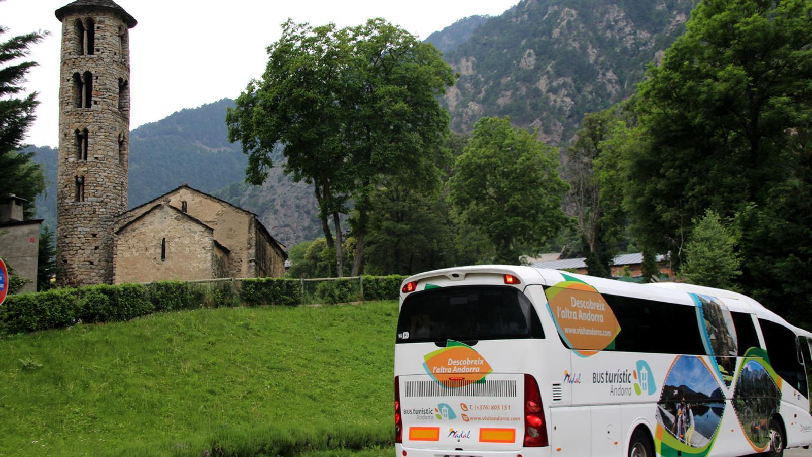 El bus turístic davant de l'església de Santa Coloma, un punt de l'itinerari de dimarts. / M.M. (ANA)