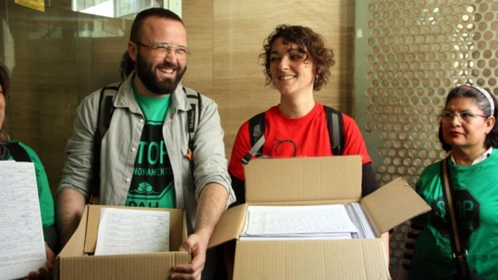 El portaveu de la PAH, Carlos Macías i la portaveu de l'Aliança contra la Pobresa Energètica, Maria Campuzano quan van entregar les primeres 40.000 firmes recollides / Raquel Garcia ACN