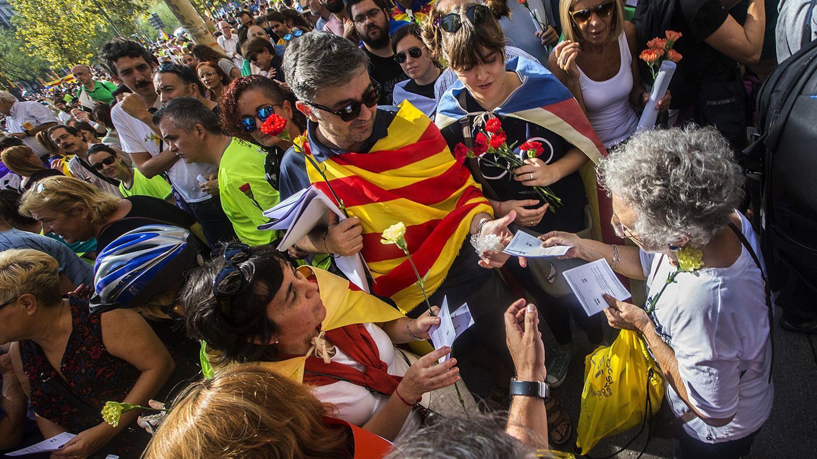 Un home reparteix paperetes a la plaça Universitat a Barcelona