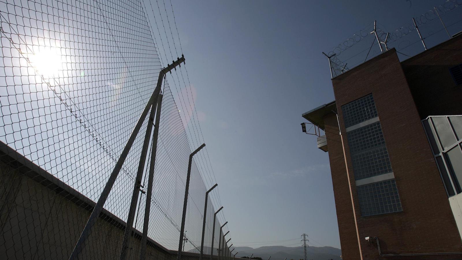 La tanca de la presó de Can Brians 2, amb un dels mòduls dels presos al fons.