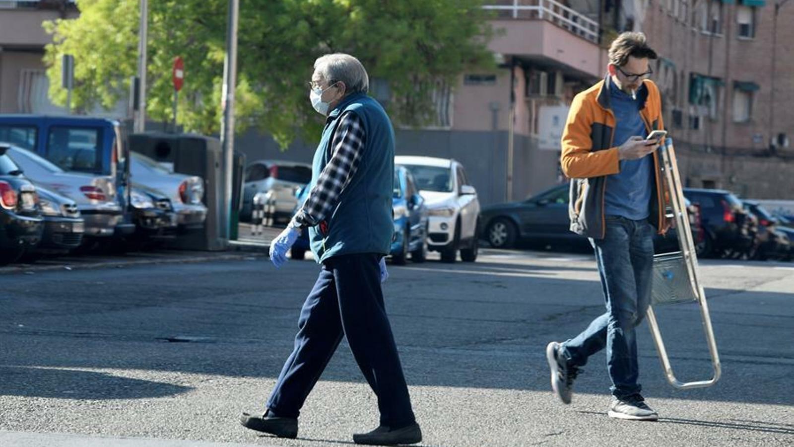 Dos veïns del barri madrileny de de Vallecas aquest dissabte passejant pel carrer