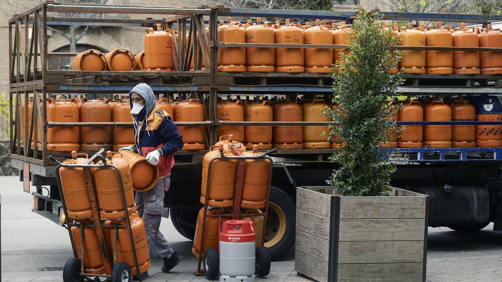 Un repartidor carregant per al servei a domicili bombones de gas butà d'un camió en un carrer de Cornellà de Llobregat.