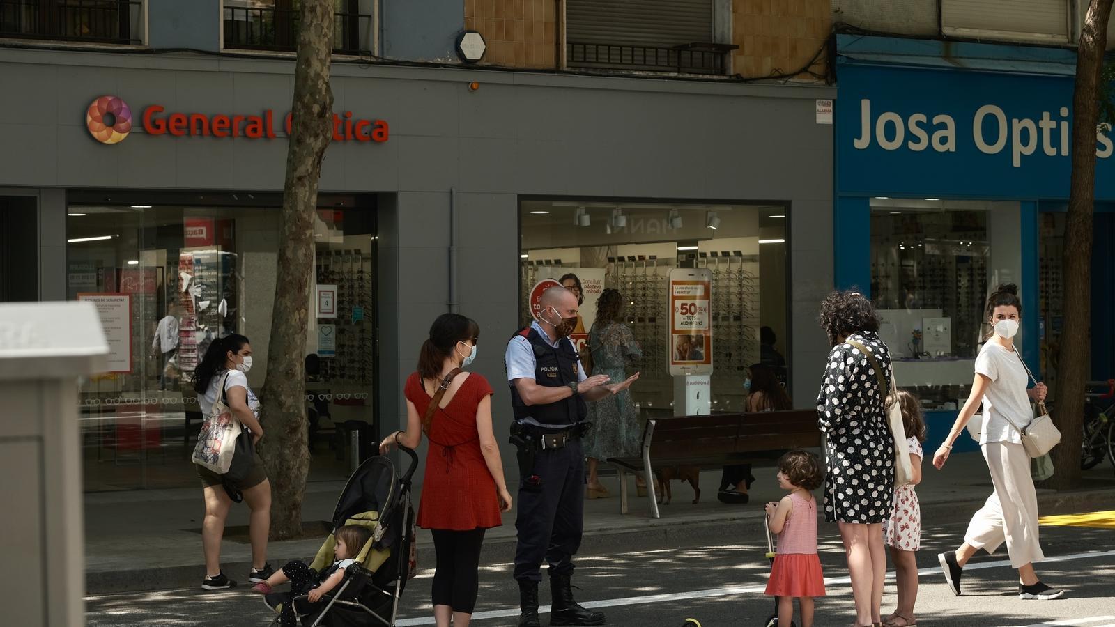 Un mosso parlant amb vianants al carrer de la Creu Coberta sense cotxes