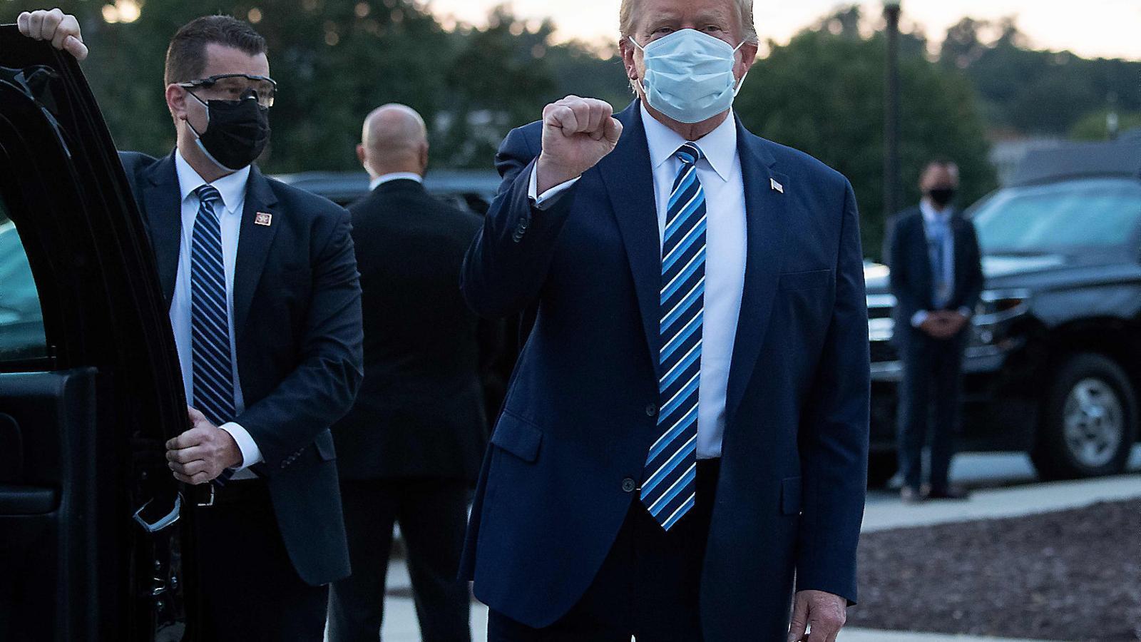 Donald Trump fent un gest amb el puny en el moment de sortir de l'hospital dilluns passat.