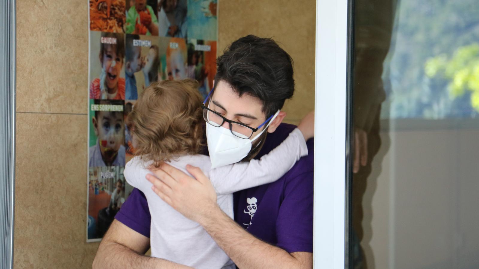 Un professor saluda efusivament una nena de l'escola bressol Conxita Mora. / E.C. (ANA)