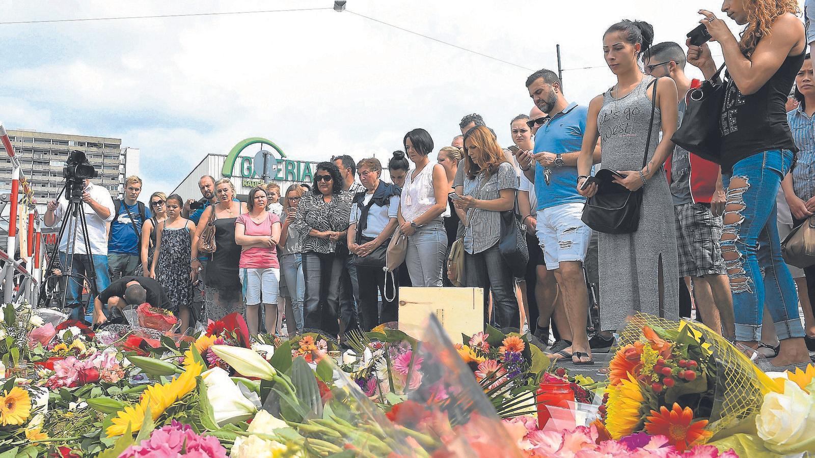 Divereses persones s'han acostat al lloc del tiroteig aquest dissabte per homenatjar les víctimes