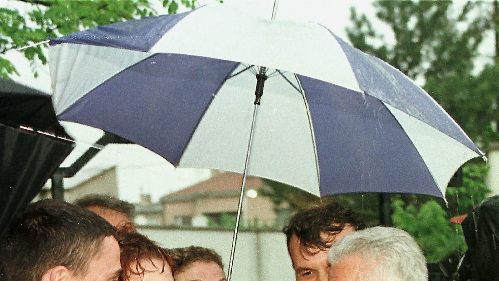 Fehmi Agani, amb gavardina sota el paraigua, parlant amb la premsa després d'una reunió de la Lliga Democràtica de Kosovo el maig del 1998, un any abans que el matessin.