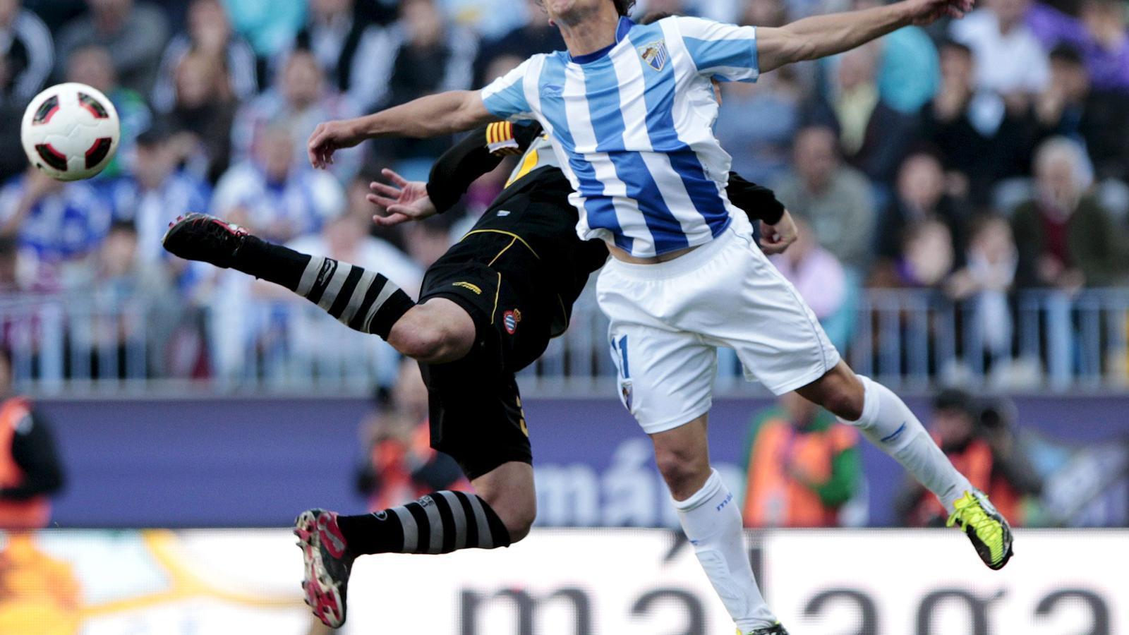 El capità de l'Espanyol, David García, vola amb Seba per una pilota. El lateral esquerre va ser el millor d'una línia defensiva a la qual es va exigir molt a Màlaga. / JORGE ZAPATA / EFE