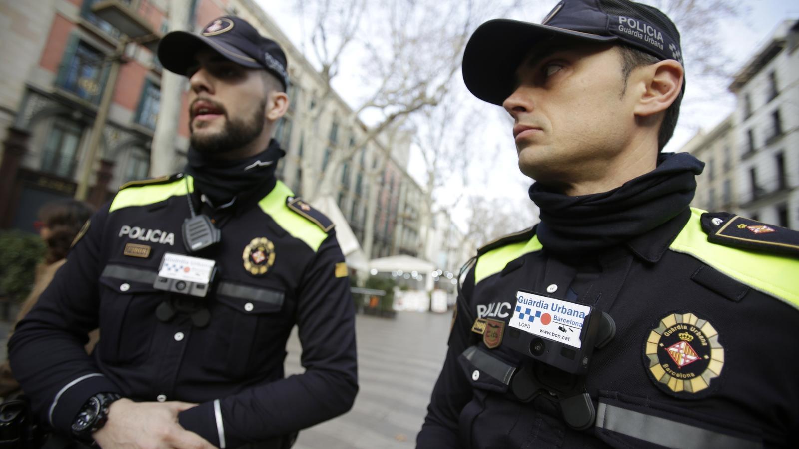Dos agents de la Guàrdia Urbana de Barcelona amb un dels models de càmeres unipersonals al pit