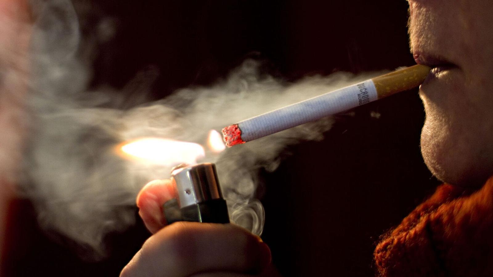 Una dona encenent-se una cigarreta en una imatge d'arxiu.