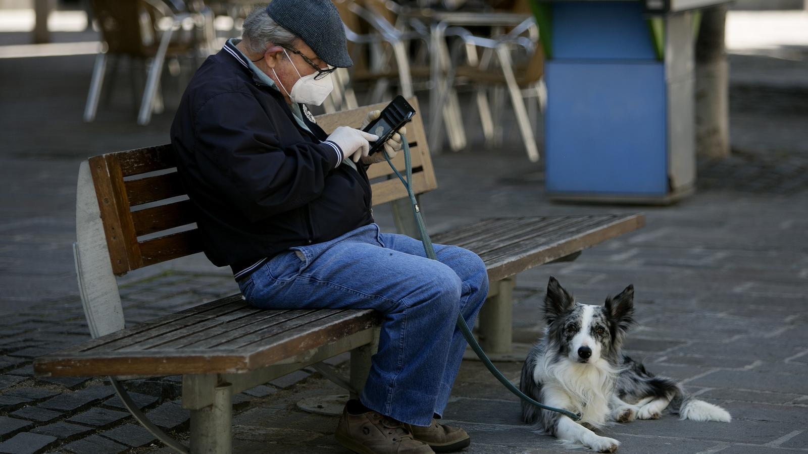 Un home consultant el seu mòbil, assegut en una plaça de Barcelona