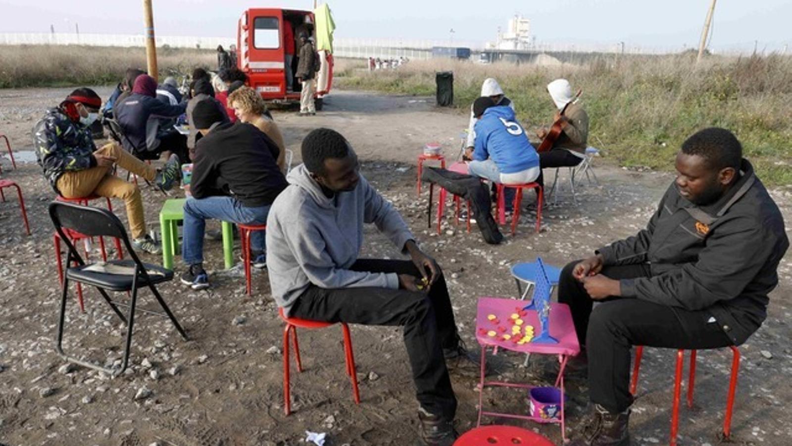 Grups de migrants passen les hores jugant mentre esperen el tancament de la 'Jungla'.