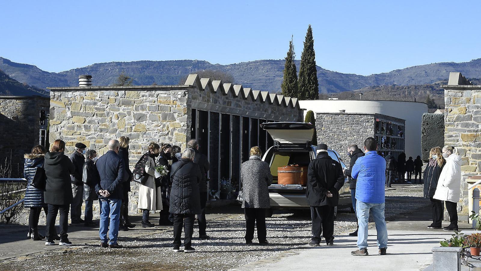 Familiars i amistats d'una persona morta per coronavirus a la residència Fiella escoltant les absoltes que mossèn Joan Antoni Mateo resava davant del vehicle fúnebre al cementiri de Tremp dimecres passat.